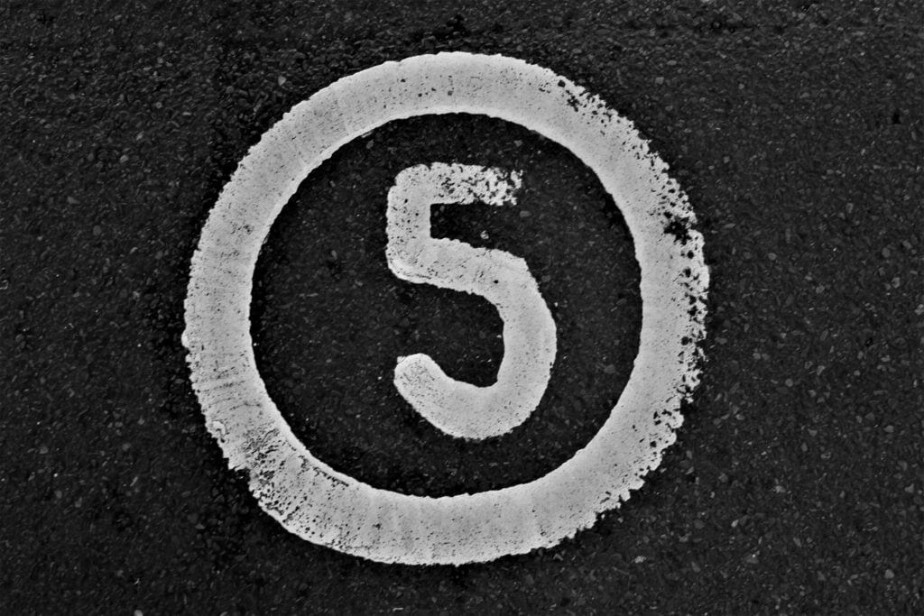 the number in 5 in white paint on black background