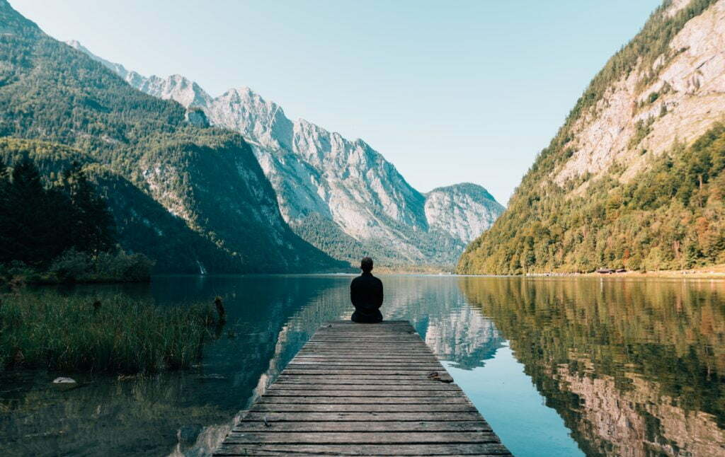 man sitting on dock looking at water and mountains
