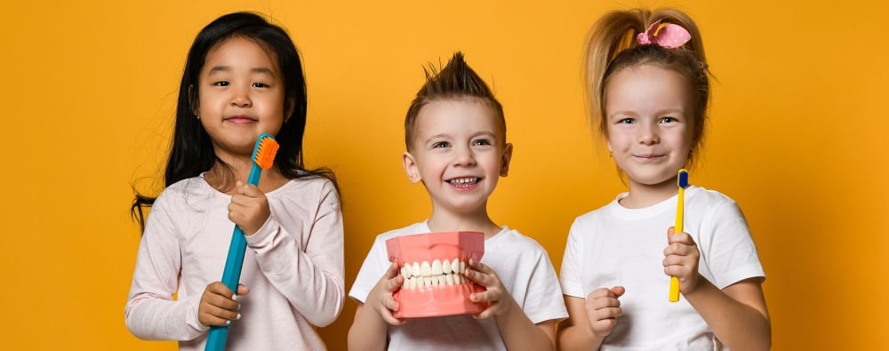 diverse kids with oral health supplies